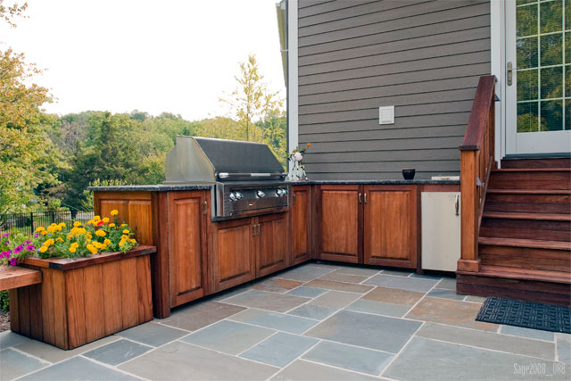Bluestone pavers set in concrete patio with an outdoor for Cedar outdoor kitchen cabinets