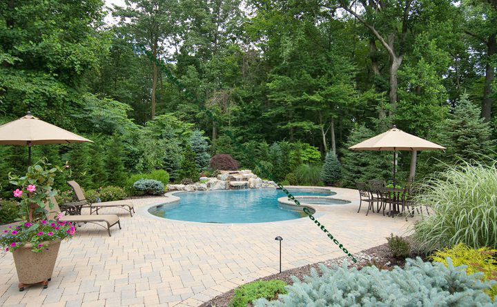 Pool Features Natural Stone Waterfalls W/ Rock Boulders, Paver Stone Pool  Patio, Landscape Shrubbery, Landscape Lighting, And Seasonal Pool Plantings.